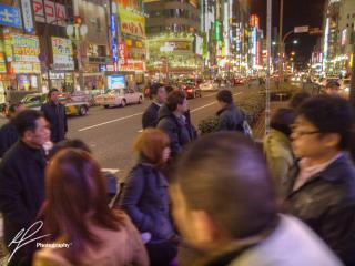 Getting lost in the nighttime atmosphere amidst the bright lights of the Shinjuku district in Tokyo, Japan.
