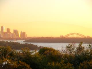 A view west from the Vaucluse headland towards the famous Sydney Harbour Bridge as the sun begins to set to the west.